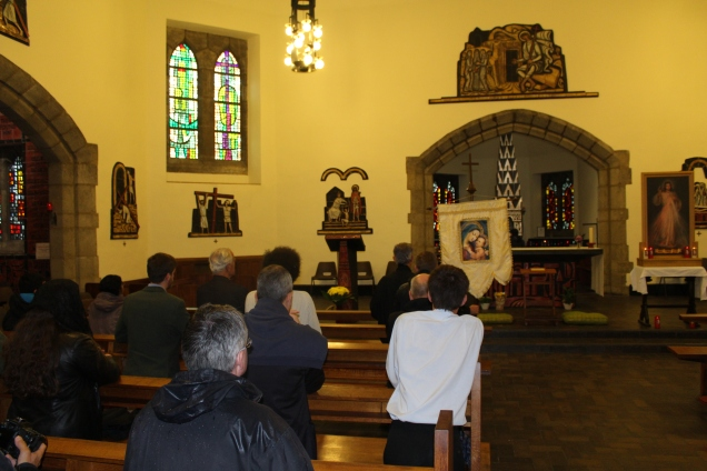 Reciting the Rosary in front of the reliquary of St Simon Stock in Aylesford. The reliquary can be seen in the background behind the altar.